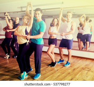 Positive dancing couples learning salsa at dance hall