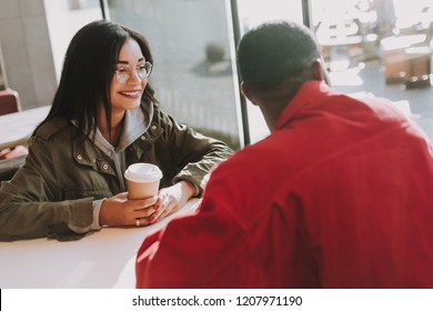 Positive dark haired lady smiling happily and holding cup of coffee while sitting next to the window with her beloved man