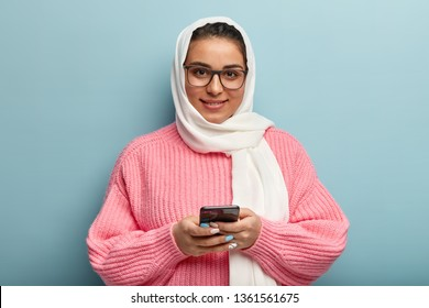 Positive dark haired smiling ethnic girl belongs to Muslims, uses modern cell phone for browsing internet, wears oversized knitted pink jumper and headscarf, waits for feedback, isolated on blue