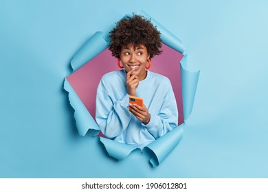 Positive dark skinned attractive woman with curly hair holds mobile phone smiles gladfully thinks about message content wears casual jumper breaks through paper background of blue studio wall