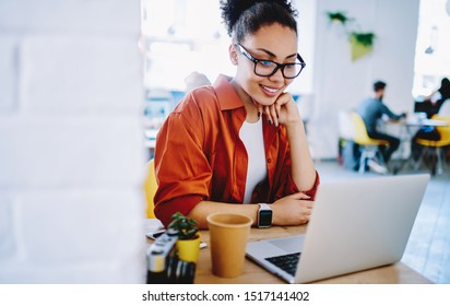 Positive dark skinned hipster girl enjoying friendly video call on laptop computer using web camera for communicating, happy woman watching comedy video on netbook during free time on leisure