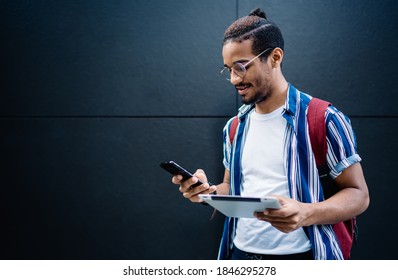 Positive dark skinned hipster guy dialing number on smartphone while holding digital tablet connected to 4G information, young african american male sending mails and messages standing on urban wall