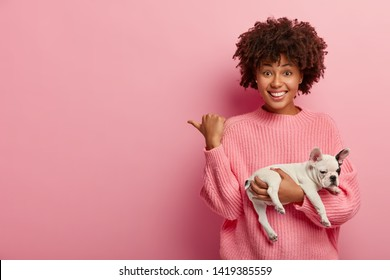Positive dark skinned lady points thumb away, wears casual jumper, holds sleeping dog, being caring hostess, shows direction to animal shop, isolated over pink background. Pedigree puppy with owner