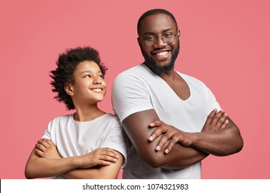 Positive dark skinned male with shining smile keeps hands crossed stands back to attractive African American teenager, have good intention, isolated over pink background. Friendship concept.