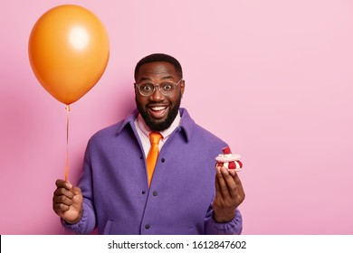 Positive dark skinned man glad to celebrate holiday, holds airballoon and cupcake, spends free time on party, smiles broadly, dressed in formal clothes, isolated over pastel rosy studio background