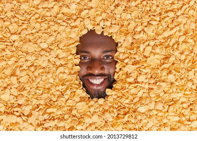 Positive dark skinned man with thick beard buried in dry cornflakes smiles pleasantly going to prepare traditional breakfast eats healthy food has delicious snack. Tasty cereals around human face