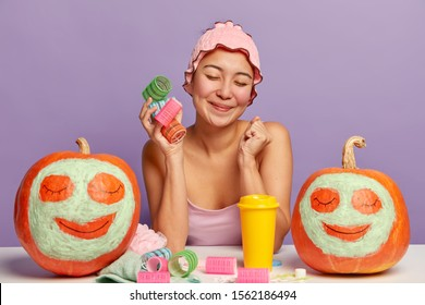Positive dark skinned woman clenches fist with pleasure has tender smile, holds colorful curlers, going to make hairstyle, poses at table in own room, yellow cup of coffee, pumpkins with applied cream