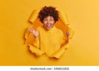 Positive dark skinned young woman with curly hair raises palm and giggles happily wears casual sweater stands through paper hole expresses glad emotions. People emotions and reaction concept
