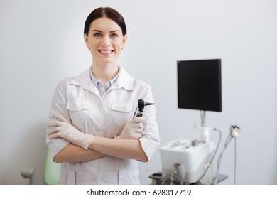 Positive delighted female otolaryngologist posing on camera