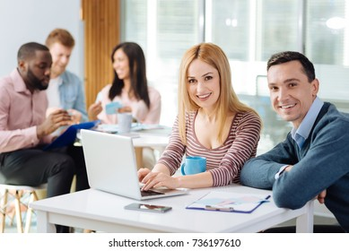 Positive delighted female person helping her coworker