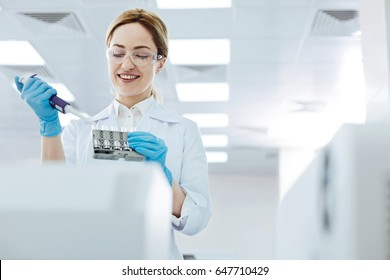 Positive delighted female scientist doing experiment