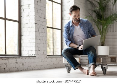 Positive delighted man holding a laptop on his knees