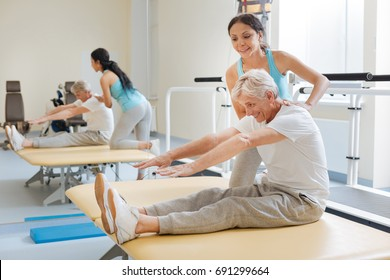 Positive delighted retirement doing stretching exercises