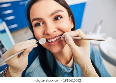 Positive delighted woman sitting in cabinet of her dentist while doing checkup