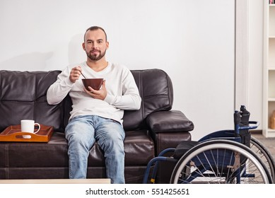 Positive disabled man having cereal in the living room