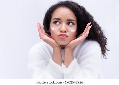 Positive dreamy young mixed race ethnicity girl apply moisturizing cream, make funny face, curly biracial girl on gray background use cleaning cosmetic product for skin washing, skincare routine.