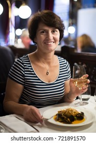 Positive elderly woman sits at table at restaurant and holds glass with wine
