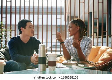 Positive emotional young businesswoman discussing news and ideas with colleague at meeting - Shutterstock ID 1688328106