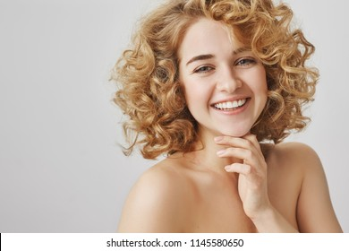 Positive emotions, beauty and skincare concept. Happy attractive young woman with curly blonde hair gently touching chin and laughing, standing naked over gray background, applying shower gel