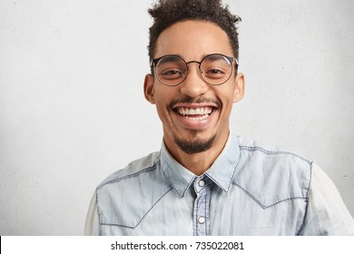 Positive emotions, facial expressions and happiness concept. Joyful man with oval face, mustache and beard smiles broadly, shows white perfect teeth, hears funny story or anecdote told by best friend
