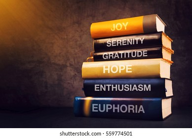 Positive emotions and feelings concept with book titles on library shelf - joy, serenity, gratitude, hope, enthusiasm and euphoria