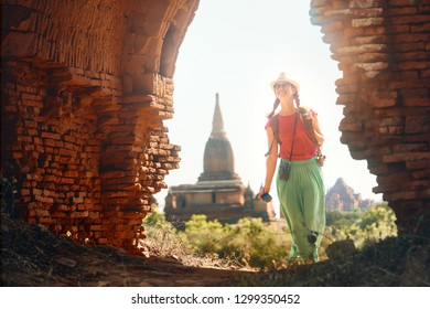 Positive emotions. Happy woman traveler with a backpack walking through the Old Bagan looking the ancient Buddhist stupas. Myanmar. Concept of travel and adventure in Asia.