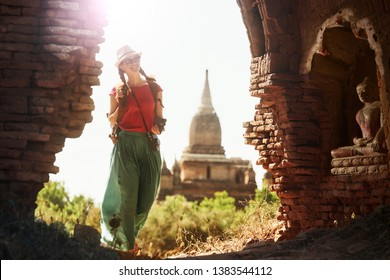 Positive emotions. Happy woman traveler with backpack walking through the Bagan looking the ancient Buddhist stupas. Myanmar. Concept of travel and adventure in Asia.