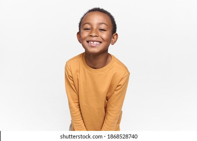 Positive emotions, joy and happy childhood. Adorable black boy posing against blank white copy space studio wall background, looking at camera with broad cheerful smile, anticipating holidays