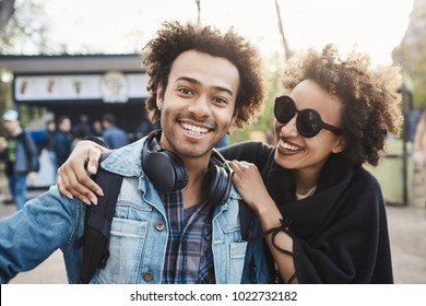 Positive and emotive young african-american people cuddling or hugging while walking in park, joking and being in good mood, wearing trendy outfit. Friendship lasts forever