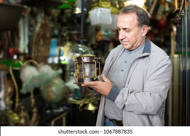 positive european adult male is choosing lamp at the market of old things.