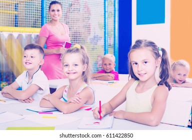 positive european children sitting together and studying in class at school