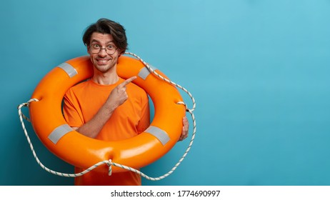 Positive European man lifesaver poses with inflated orange life ring, indicates at empty space, shows way to sea or swimming pool. Lifeguard on duty holds rescue circle. Safety beach holiday.