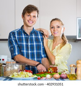 positive european man and woman standing near table  in domestic kitchen