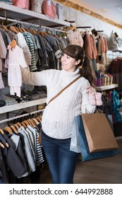 positive european  pregnant woman showing her purchases in childrenâ??s clothes shop