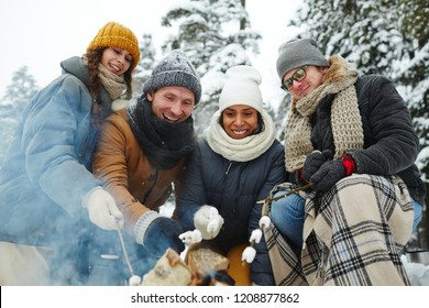 Positive excited young multi-ethnic friends in winter coats sitting by campfire and roasting marshmallows on fire at camping in forest