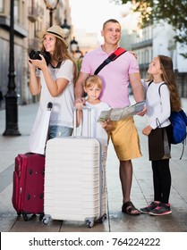Positive family with children using map and photographing sights during their vacation