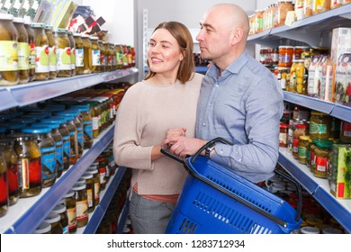 Positive family couple with basket choosing canned goods in the food store