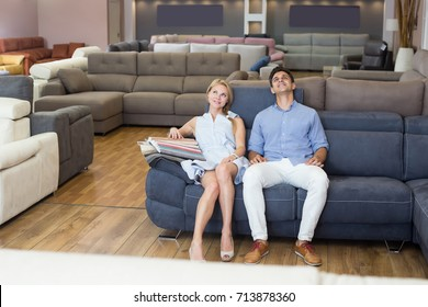 Positive family couple choosing new sofa and sitting in the furniture shop