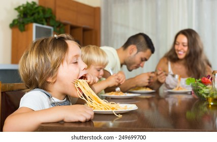 Positive family of four having lunch with spaghetti at home