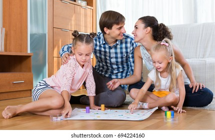 positive family playing at board game in domestic interior