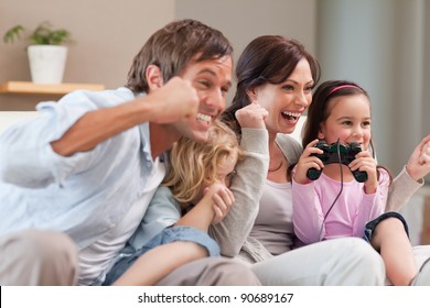 Positive family playing video games together in a living room