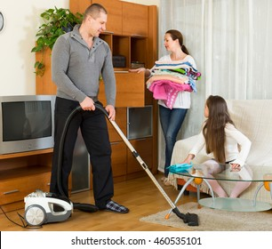 Positive family of three cleaning in the living room all together. Focus on man