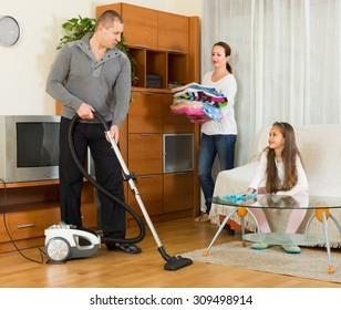 Positive family of three tidying up a room all together. Focus on man