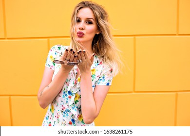 Positive fashionable portrait of cheerful blonde woman posing at yellow background wall, trendy feminine floral dress, sending air kisses to you, soft toned colors.