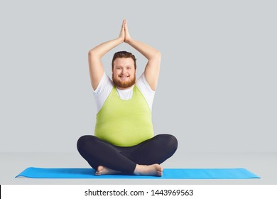 Positive fat man Yogi does yoga exercises a gray background.