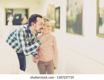 positive father and daughter regarding paintings in halls of museum