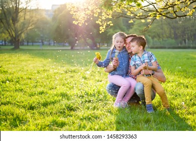 Positive father walks with his children with his son and daughter and blows dandelions sitting on the lawn in the park on a warm sunny summer day. Family weekend concept