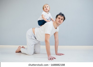 Positive father working out, doing plank exercise with his jolly toddler baby boy riding on his neck. Middle age man on knees at table pose playing with his son. Full body.