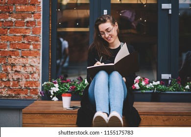 Positive female author writing essay with excited idea in notebook while sitting on publicity area and smiling, joyful hipster girl feeling happy of studying outdoors notes plan in textbook