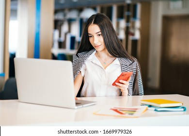Positive female blogger is reading comments under post in social networks on modern telephone while sitting in cafe. Attractive woman in formal wear is working using laptop computer.